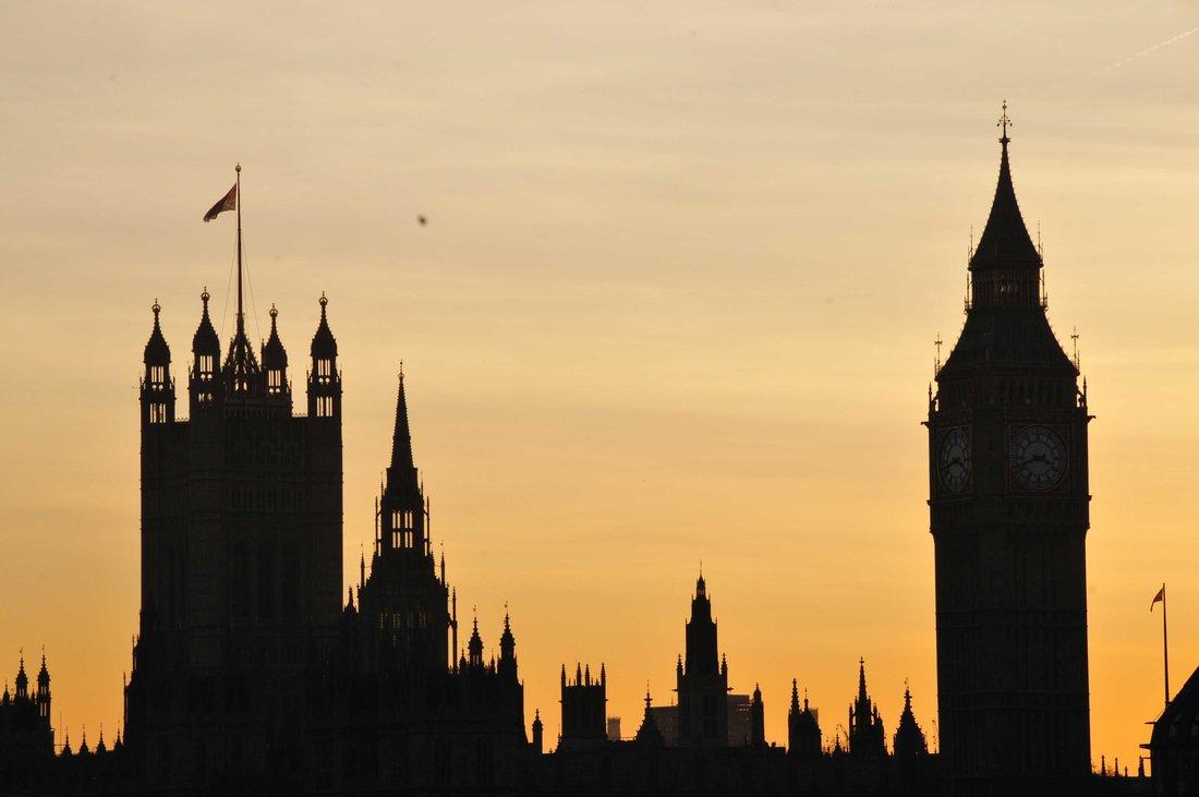 Vue des silhouettes du parlement de Londres et de Big Ben à travers un coucher de soleil.