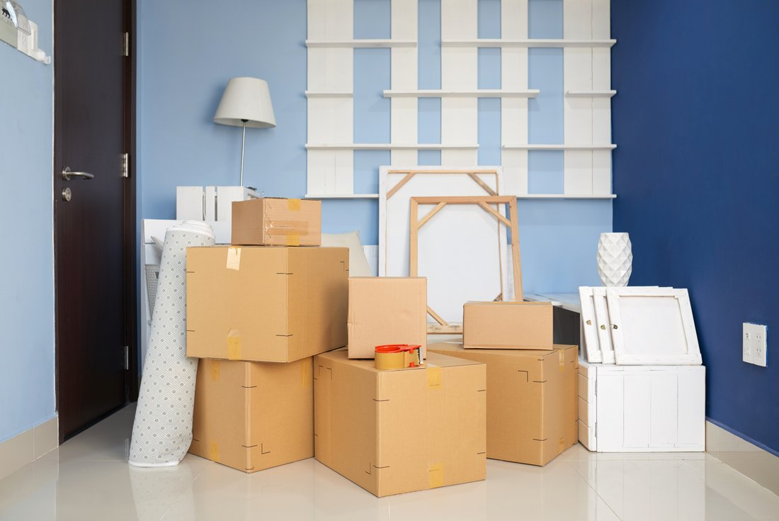 Moving boxes and decorative objects are stacked in a room with blue walls.