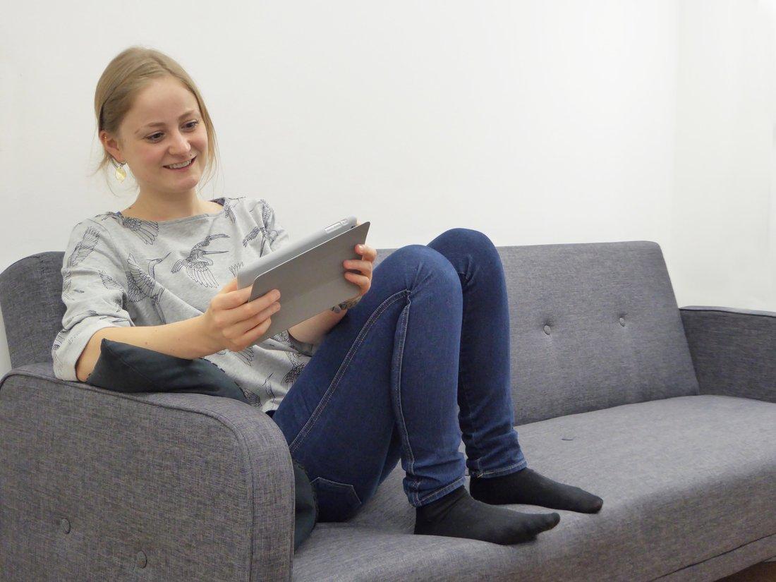 Une jeune femme souriante, assise sur un canapé tient dans ses mains une tablette numérique.