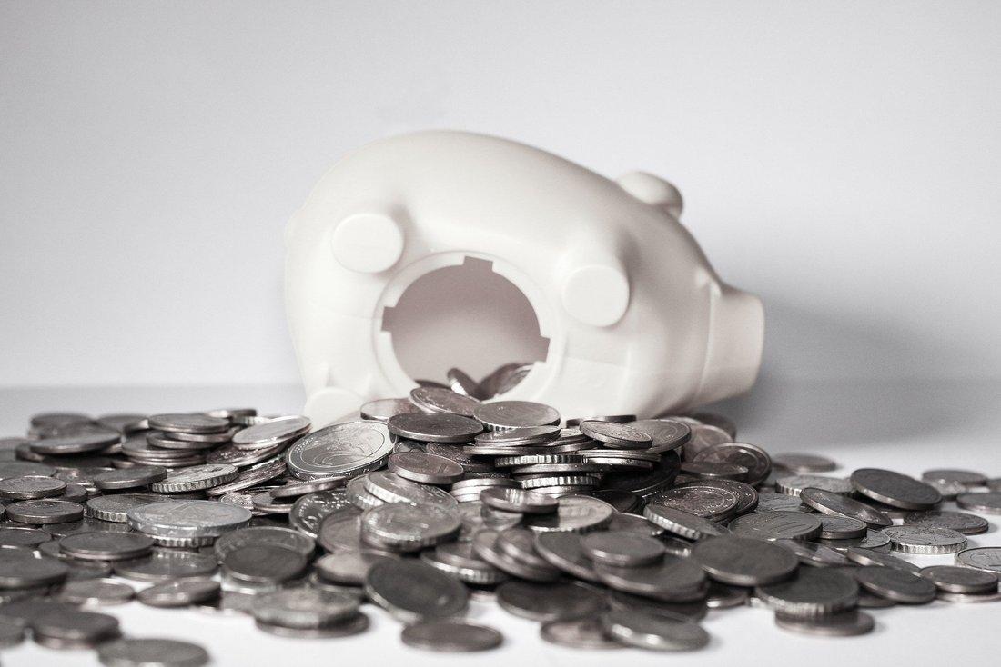 Une tirelire en forme de cochon est ouverte et de nombreuses pièces de monnaies sont étalées tout autour.