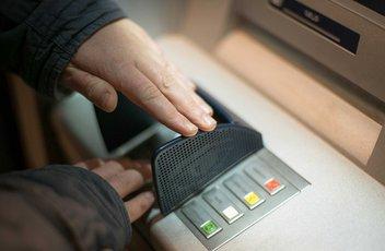 Une personne est en train de cacher le pavé numérique sur le distributeur de billet pendant qu'elle compose son numéro.