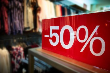 "Close-up of a sale sign indicating ""-50%"" in a clothing shop."