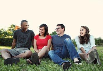 sourire de jeunes femmes et hommes assis sur l'herbe