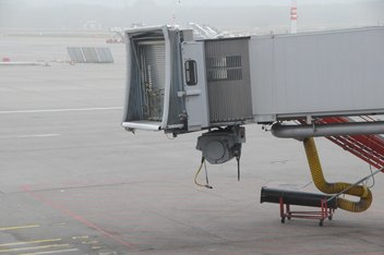 Unused boarding bridge on the tarmac of an airport.