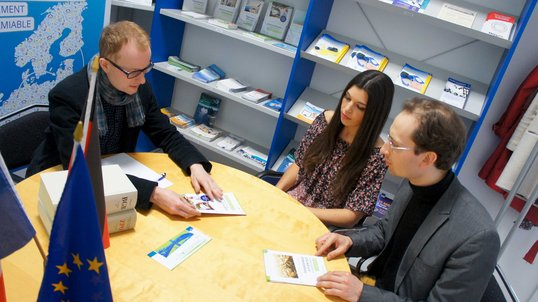 A consultation around a table between two consumers and a legal adviser, who hands them a brochure.