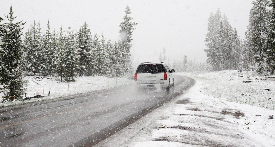 Une voiture roule sur une route au milieu d'un paysage enneigée.