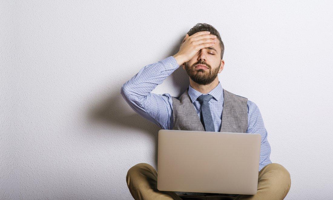 Un homme assis avec son ordinateur portable sur les genoux tient sa tête avec sa main.