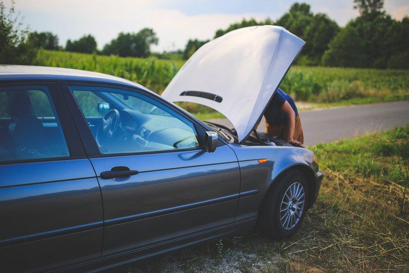 Un homme est en train de réparer une voiture, le capot ouvert, sur le bord d'une route de campagne.