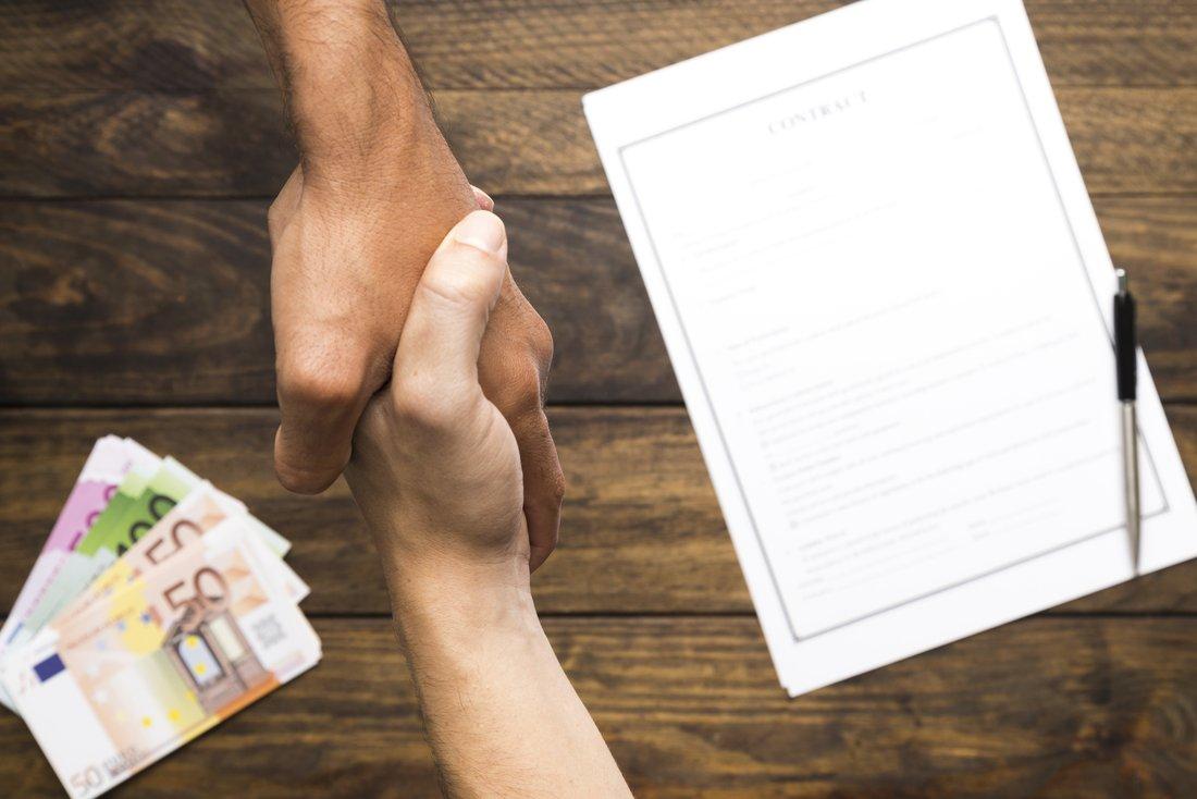 Deux personnes se serrent la main, on peut voir en arrière plan un contrat ainsi que plusieurs billets.