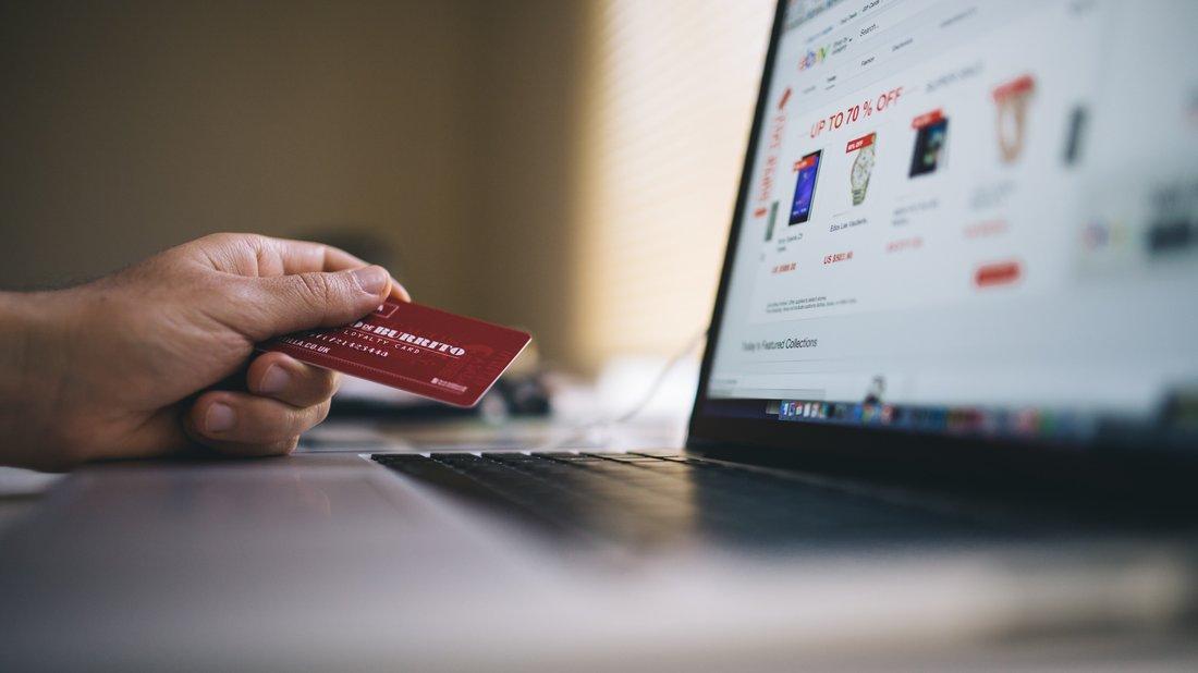 Une personne est devant son ordinateur, sur un site de e-commerce, et tient dans sa main une carte de crédit.