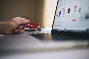 A person is in front of his computer, on an e-commerce site, holding a credit card without in hand.