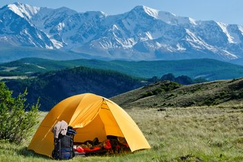 A tent is set up in the nature, with mountains in the background.