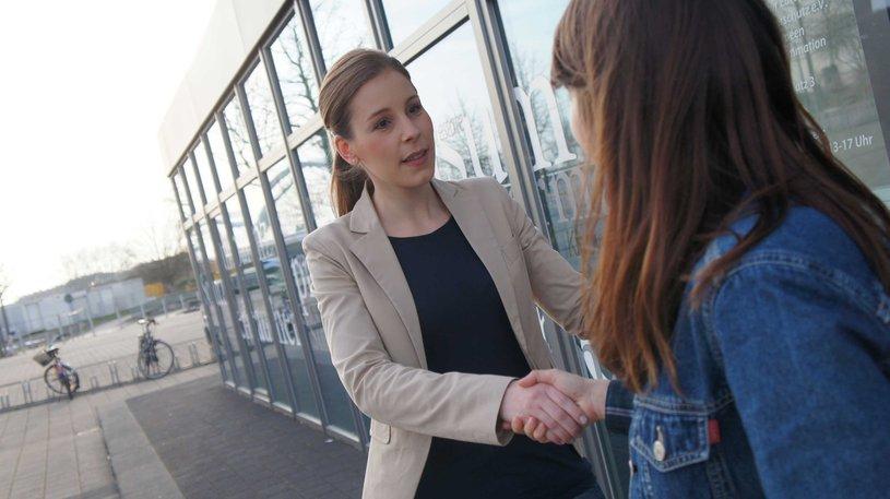 Deux femmes se serrent la main.