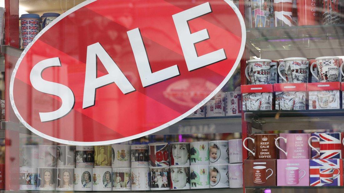"""Une mention """"soldes"""" est collée sur une vitrine de boutique de souvenirs."""