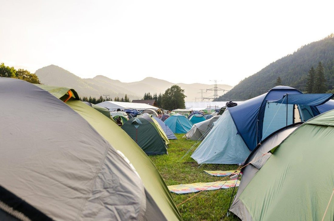 Tents set up on a campground in a mountainous region.