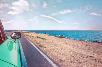 Une voiture verte roule le long d'une côte : on peut voir la mer à côté de la route.