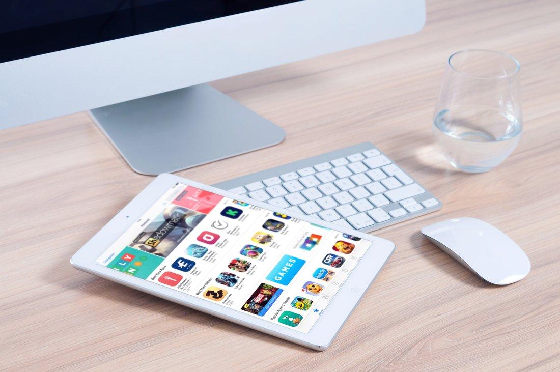 Un ordinateur et une tablette avec l'écran allumé posés sur un bureau.