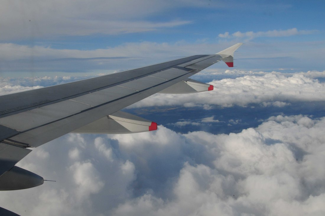 View of the wing of an airplane in full flight with clouds in the background.