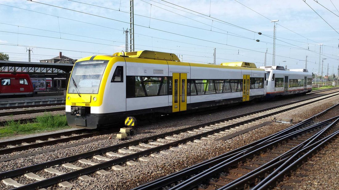 A yellow train stopped in the middle of several rails