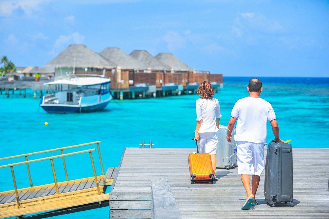 Un couple qui marche valises à la main sur une passerelle au dessus d'une eau turquoise. On voir en arrière plan des bungalow en bois et en paille.