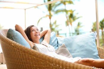Une femme souriante est étendue au soleil, sur un grand fauteuil en osier rempli de coussins. On peut voir des palmiers en arrière-plan.