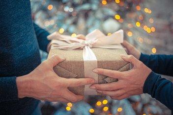 Un homme donne un cadeau emballé à une femme, avec un sapin de Noël illuminé en arrière plan.
