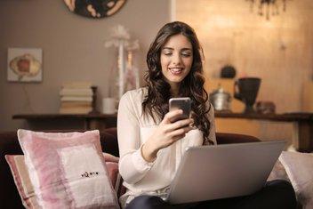 Une femme souriante assise sur un canapé tient son téléphone portable dans les mains et son ordinateur sur les genoux.
