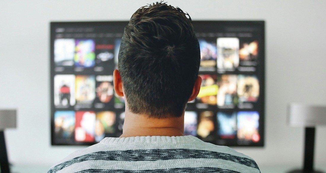 Un homme, vu de dos qui regarde un écran de télévision.