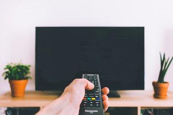 Gros plan sur une personne qui pointe la télécommande vers la télévision.
