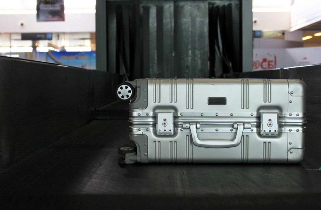 A silver suitcase is placed on the conveyor belt to be checked and checked in at boarding.
