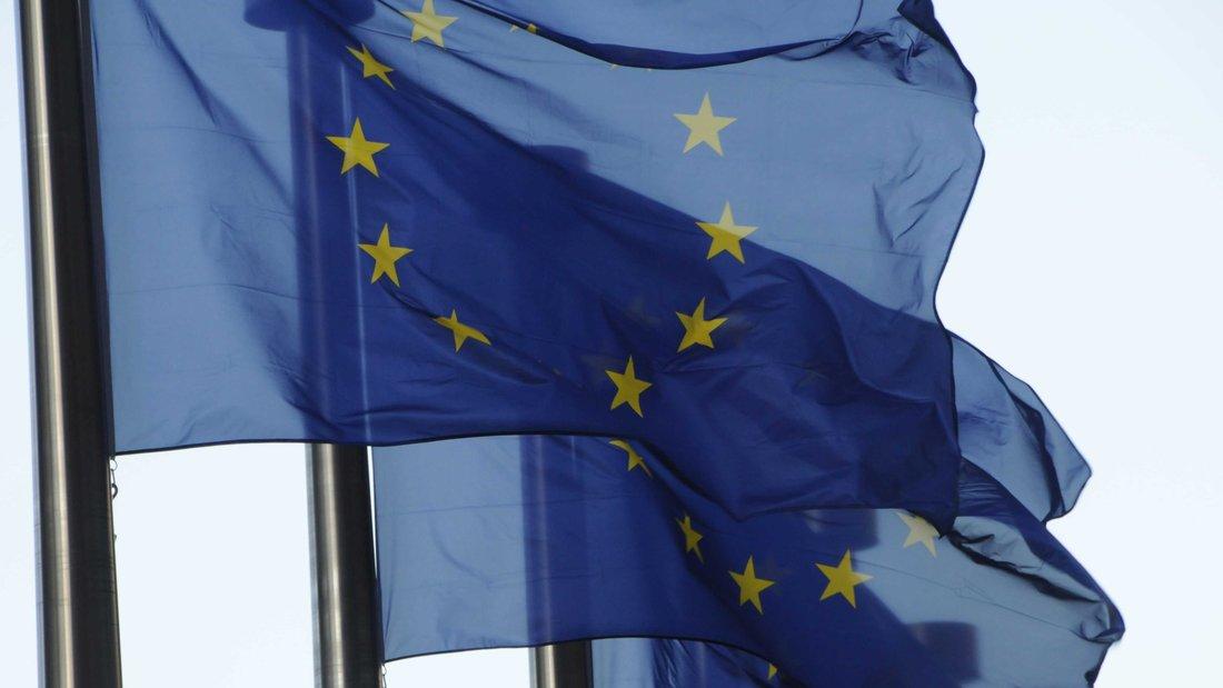 Trois drapeaux européens alignés flottent dans le vent.