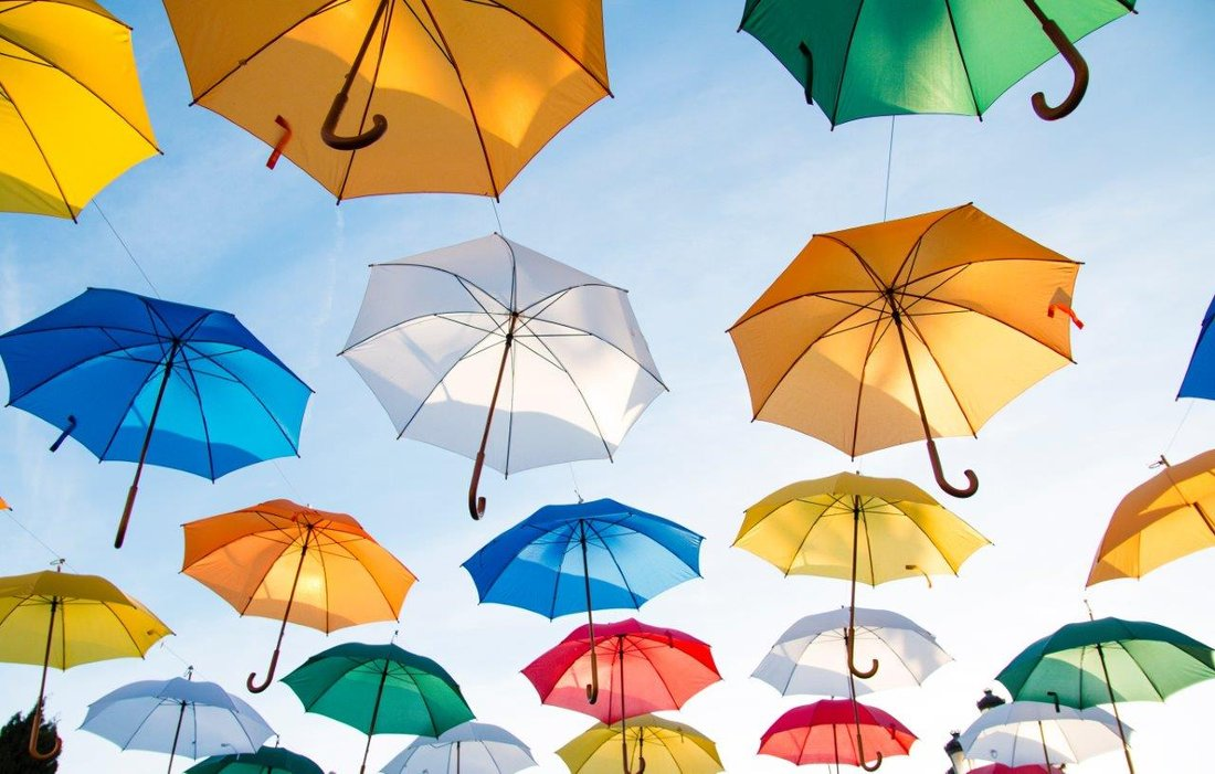 Colourful umbrellas are suspended open to a blue sky in the background.