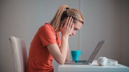 Femme assise devant un ordinateur portable se tenant la tête