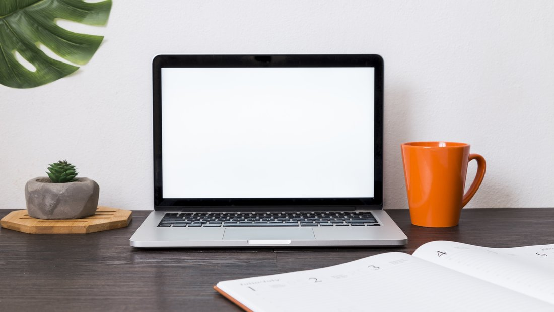 Vue sur un espace de travail avec un ordinateur portable, un agenda, une tasse.