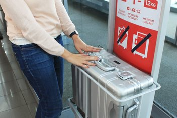 A woman verifies that her suitcase conforms to the boarding rules.