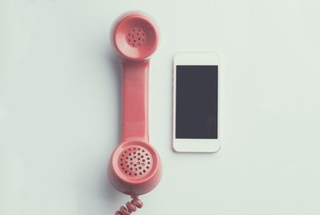 A smartphone is placed next to a vintage phone with pink wire.