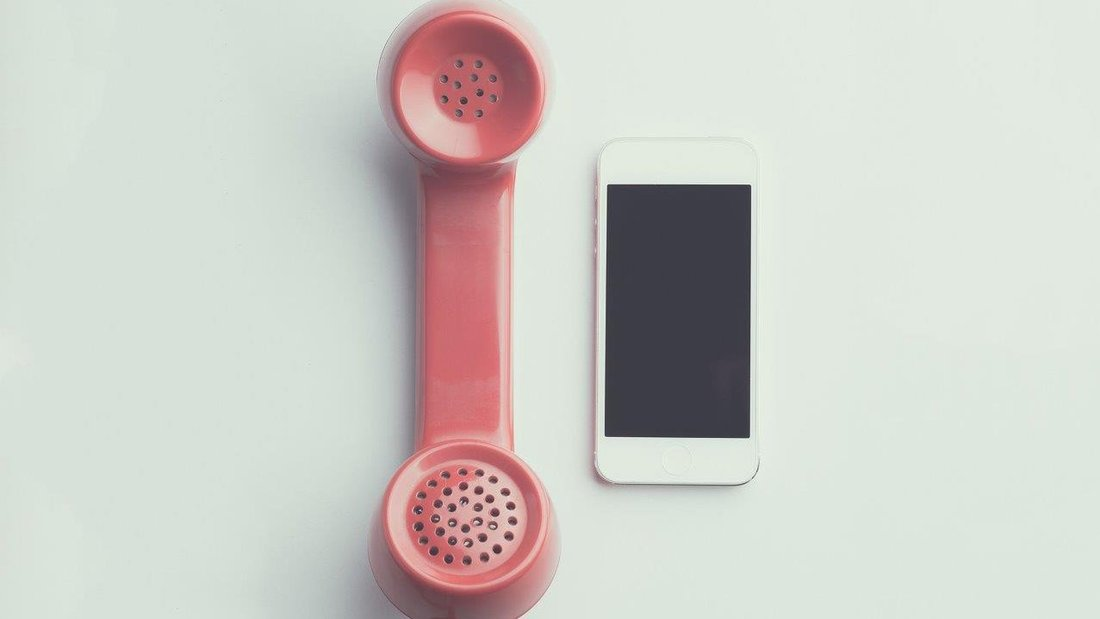 Un smartphone est posé à côté d'un téléphone vintage à fil de couleur rose.