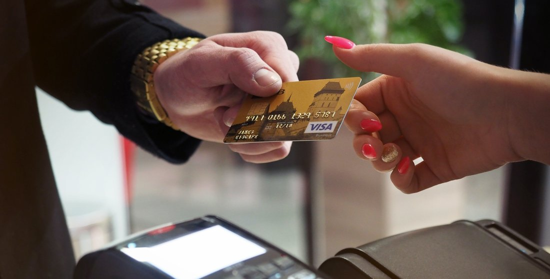 A man gives his bank card to a woman who holds a bank terminal for payment.