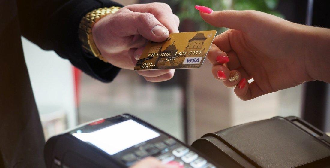 Un homme donne sa carte bancaire à une femme qui tient un terminal bancaire pour le paiement.