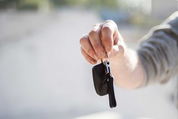A person's hand holds out car keys.
