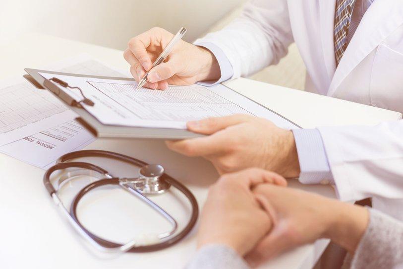 Un docteur rempli un formulaire, un patient se tient à côté de lui.