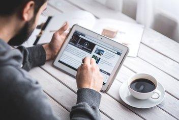 Un homme navigue sur sa tablette, une tasse de café à côté de lui.