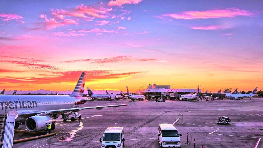 Vue sur la piste d'atterrissage d'un aéroport avec de nombreux avions et véhicules.
