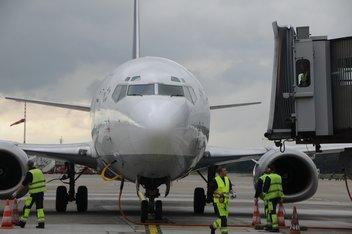 Un avion vu de face à l'arrêt sur la piste d'atterrissage, préparé par les techniciens de l'aéroport.